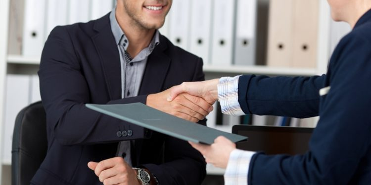 a boss shakes the hand of a new-hire customer service in education