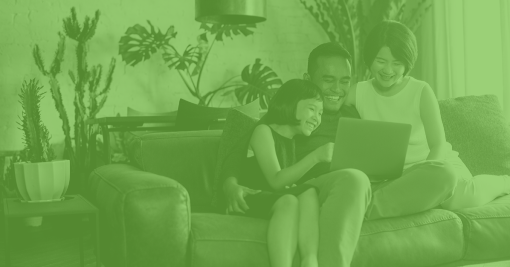 Family sitting in their living room doing something on a computer online school registration social distancing